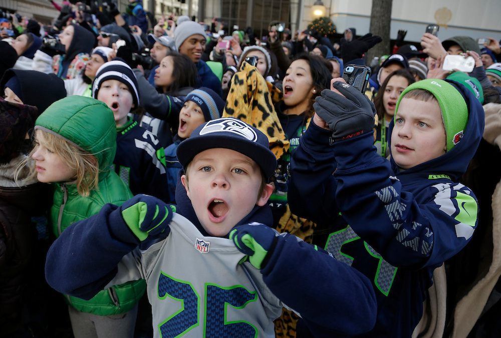 Young Seahawks fans cheer at the Super Bowl victory parade for the Seattle Seahawks in Seattle, Washington February 5, 2014. Up to 500,000 Seattle Seahawks fans were expected to brave sub-freezing temperatures to celebrate the football team's first Super Bowl title at a parade set to wind through the city's downtown on Wednesday.  REUTERS/Jason Redmond  (UNITED STATES)