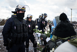 © London News Pictures. Calais, France. 07/03/16. A refugee child tries to hand a white flower to French riot police in an attempt to halt the demolition. French authorities are evicting and demolishing the southern half of the Calais 'Jungle' camp, which charities estimate to contain 3,500 people. . Photo credit: Rob Pinney/LNP