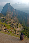A tourist is admiring the lost Inca city of Machu Picchu. Now one of the seven new wonders of the modern world. It is located in Cusco, Peru