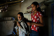 Pooja, 14, a student from the village of Pathpuri, Hoshangabad, Madhya Pradesh, India, taking part to the children's journal, a project launched by Dalit Sangh, an NGO which has been working for the uplift of scheduled castes for the past 22 years, is helping her younger brother Narendra Kumar, 9, preparing for school, in their home. Dalit Sangh is working in collaboration with Unicef India to promote education and awareness within backward communities.