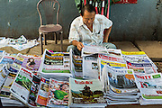 17 JUNE 2013 - YANGON, MYANMAR: A man at a newsstand reads a newspaper. The Burmese newspaper industry has enjoyed explosive growth this year after private ownership was allowed in 2013. Private newspapers were shut down under former Burmese leader Ne Win in the early 1960s. The revitalized private press is a sign of the dramatic changes sweeping Myanmar, formerly Burma, in the last three years.      PHOTO BY JACK KURTZ