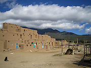 Adobe houses with colorful doors at Taos Pueblo, New Mexico. Interesting with the two dogs staring at eachother!