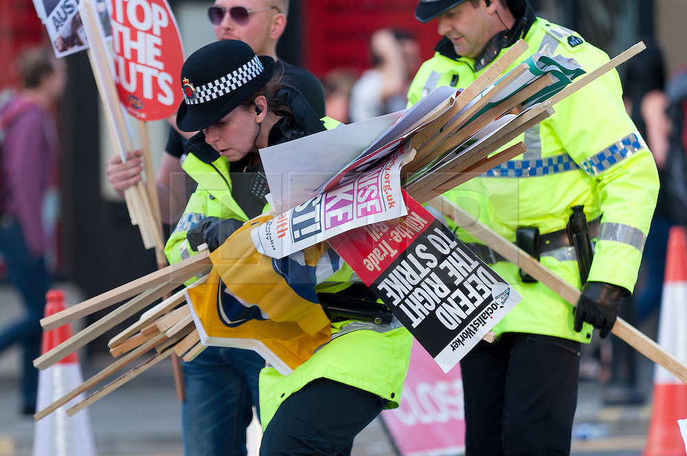 © Licensed to London News Pictures. 04/10/2015. Police help with the clearup. An estimated 85 thousand take part in a National Demonstration march through the city. A week of pro-peace, anti-austerity, anti-war, anti-Tory, protests dubbed 'Take Back Manchester' has been  organised by The People's Assembly and timed to coincide with the Conservative Party Conference in Manchester on 4th - 7th Oct 2015. Over 40 events are planned, including a speech by new Labour leader Jeremy Corbyn timed to compete with closing speech of Tory leader David Cameron. Photo credit: Graham M. Lawrence/LNP