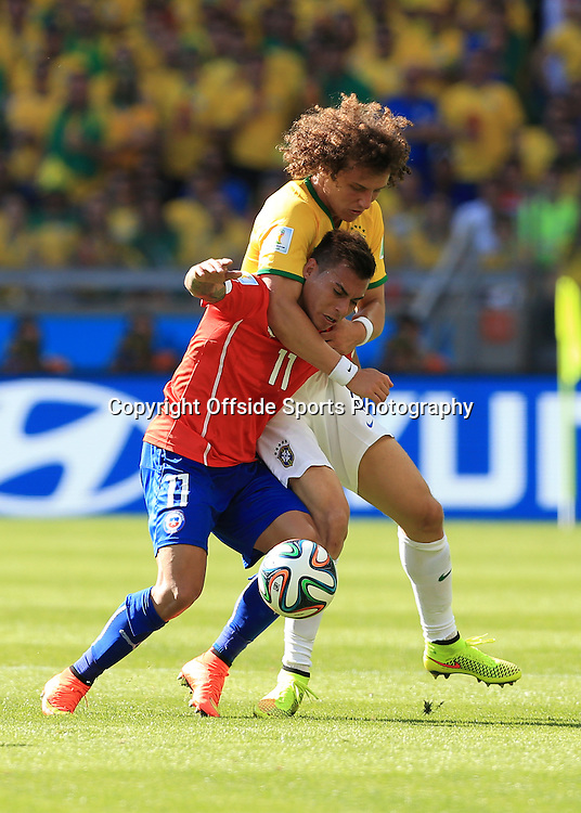 28th June 2014 - FIFA World Cup - Round of 16 - Brazil v Chile - David Luiz of Brazil drags down Eduardo Vargas of Chile - Photo: Simon Stacpoole / Offside.