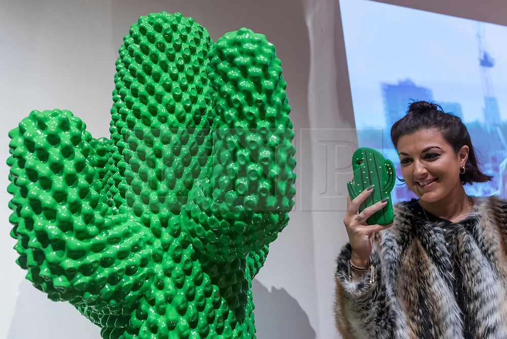 "© Licensed to London News Pictures. 06/11/2018. LONDON, UK. A visitor views ""Gufram Cactus"", 1972, by Guido Drocco and Franco Mello. Preview of ""Home Futures"", at the Design Museum.  The exhibition, in partnership with IKEA Museum Almhult, asks are we living in the way that pioneering architects and designers once predicted, or has our idea of home proved resistant to real change?  More than 150 objects and experiences are on display 7 November to 24 March 2019.  Photo credit: Stephen Chung/LNP"