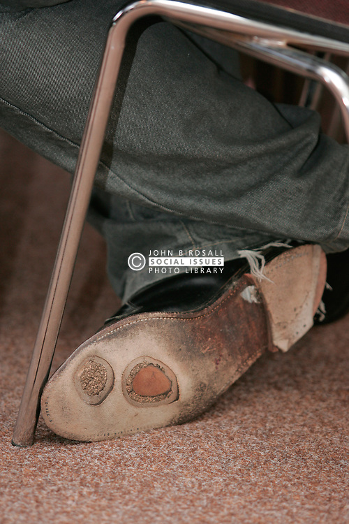 Holes on the soles of a man's shoe at centre for unemployed London UK