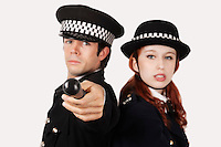 Portrait of confident police officers against gray background