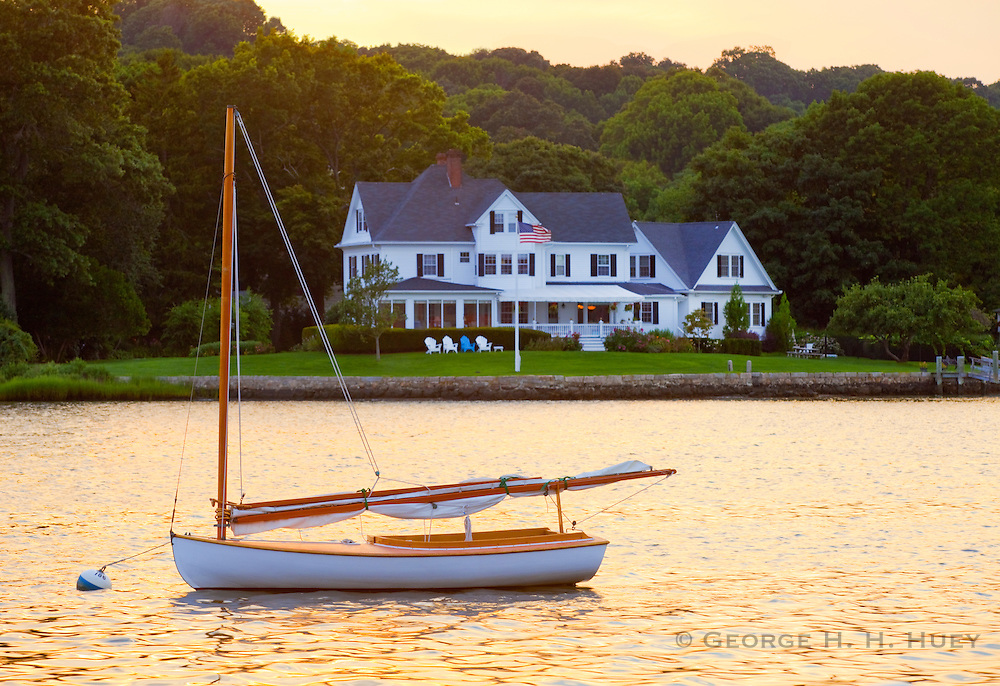 351021-1018G.Huey ~ Copyright: George H.H. Huey ~ Wooden catboat moored in the Mystic River, with historic house.  Mystic, Connecticut.