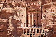 Tourists gather at the base of the Royal Tombs, carved into rock cliffs in Petra, Jordan.