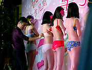 LIUZHOU, CHINA - MARCH 08: (CHINA OUT) <br /> <br /> Celebrating female power, Chinese style: Shopping mall hosts bra-undoing contest on International Women's Day <br /> <br /> A shopping mall in China seemed to have got the wrong idea when celebrating International Women's Day with a one handed bra competition.<br /> Six scantily clad female models lined up on a stage at the store in Liuzhou city on March 8, as men and women took it in turns to undo their bras using only one hand.<br /> Bizarrely the models had masks on as they stood with their backs to the crowd. The winner was a woman who managed to undo all six bras in 14 seconds. <br /> <br /> At the event, a total of eight spectators volunteered to take part in the competition, but surprisingly according to China Daily, only one of them was a man.<br /> The aim of the game was to undo each bra with one hand in the fastest time possible.<br /> Not only did the models participate in the contest, they strutted their stuff on the stage wearing only their underwear and a mask as dozens of prying customers looked on. <br /> According to the report, the contest was put on to attract more customers on International Woman's Day.<br /> But it seems whoever's idea it was to hold a one handed bra competition using nearly naked models, they may have not understood the meaning of the day.<br /> It is not clear in the report what the prize was for the winner of the competition. <br /> This is not the first time businesses in China have come under fire for 'missing the point' on International Women's Day.<br /> In 2015, two of the country's most popular websites were criticised for using 'sexist stereotypes' on the day that is celebrated by millions across the globe. <br /> Search engine Baidu had a ballerina in a pink dress, who turned into a bride and then into a mother pushing a baby, on its homepage.<br /> And video-sharing site Youku, wrote to all its female users on its page: 'May the world treat you gently.'<br /> According to the United Nations, International Women's Day on March 8 is a time to reflect on progress
