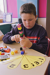 Primary school boy counting using unilink blocks and number fan in practical maths lesson,