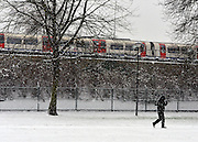 © Licensed to London News Pictures. 18/01/2013. London, UK A couple walk through a park as a Piccadilly Line tube train passes by in the snow. Snow in West London today 18th January 2013. Photo credit : Stephen Simpson/LNP