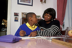 Mother helping her son with his homework UK
