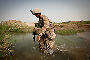 Navy Hospital Corpsman Joseph Kubat wades through a canal in Marjah.