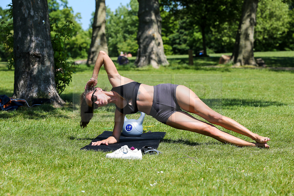 © Licensed to London News Pictures. 19/05/2020. London, UK. A woman exercises in Finsbury Park, north London on a warm and sunny day in the capital. The government has relaxed the rules on the COVID-19 lockdown, allowing people to spend more time outdoors whilst following social distancing guidelines. According to the Met Office, 27 degrees celsius is forecast for tomorrow. <br /> <br /> ***Permission Granted***<br /> <br /> Photo credit: Dinendra Haria/LNP
