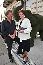 HUGO BURNAND and LADY ELIZABETH ANSON at a party to celebrate the 60th birthday of Mark Shand and the 50th birthday of Tara the elephant held at 29 Portland Place, London on 25th May 2011.