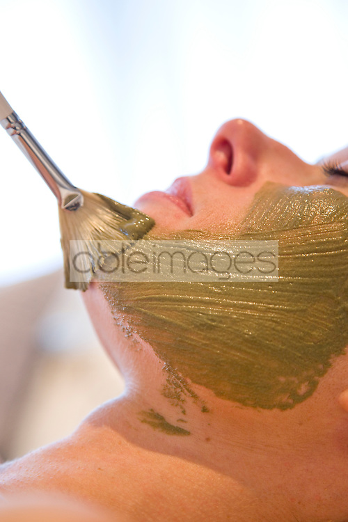 Close up of a brush on a woman face with green facial mask
