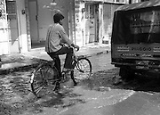 India, Tamil Nadu, Madurai cyclists rides in a puddle in the road