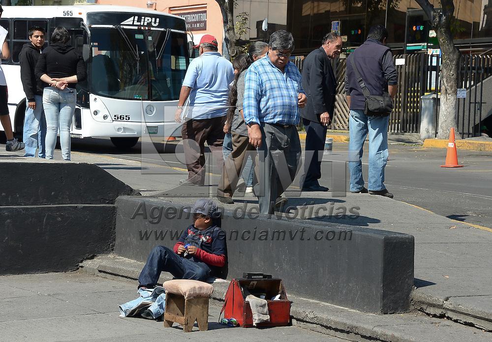 Toluca, México.- Un pequeño espera pacientemente la llegada de algún cliente que quiera lustrar su calzado, acompañando a su padre busca ayudarlo en cualquier cosa. Agencia MVT / Crisanta Espinosa