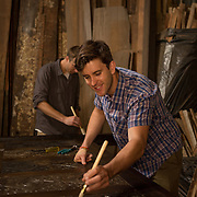 Alex Geriner, woodworker and owner/founder of Doorman Designs and employee Cody Mower (in back) in the woodshop in the Lower Garden District in New Orleans. Geriner works primarily with specifically Southern reclaimed material, such as cypress and wrought iron. For more information: http://www.doormandesigns.com