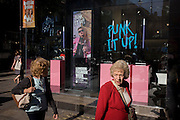 Two elderly ladies walk past a Sunglasses Hut shop whose theme is London Fashion Week's 'Punk it Up'.