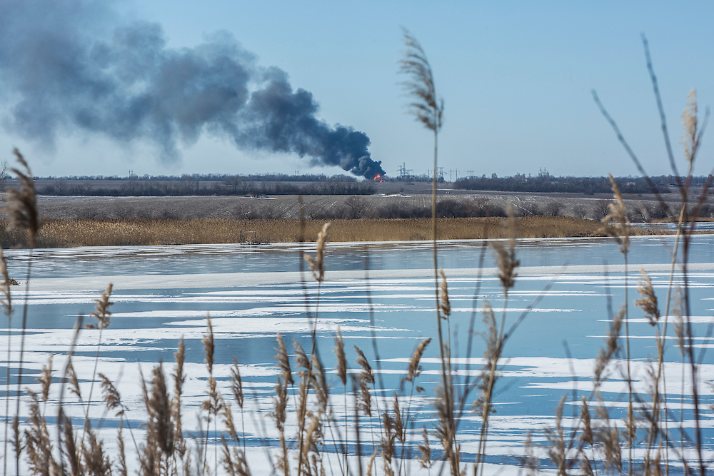 MYRONIVSKYI, UKRAINE - FEBRUARY 17: A gas pipe burns in the distance after being struck by shelling on February 17, 2015 in Myronivskyi, Ukraine. A ceasefire agreed to by Ukraine and pro-Russian rebel forces has failed to prevent fighting in the nearby town of Debaltseve, where thousands of Ukrainian troops remain and whom rebels claim to have surrounded. (Photo by Brendan Hoffman/Getty Images) *** Local Caption ***