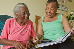 Carer and elderly visually impaired woman looking at photo album