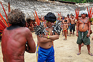 Justino - famous elder, hunter and warrior (with black painted fece) engages a dialog with the shaman and elder from the Venezuelan Yanomami Guests that arrived by plane.. This art of singing dialog is only mastered by the most talented ancients.