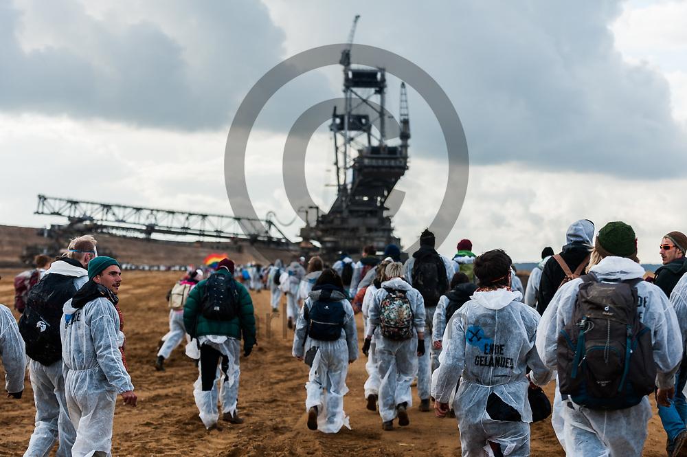 Deutschland, Elsdorf - 05.11.2017<br /> <br /> Aktivisten laufen durch die Grube auf einen Kohle Baggers zu. Circa 2500 Aktivisten drangen in die Grube des Braunkohle Tagebau Hambach ein um mit der Aktion f&uuml;r einen sofortigen Kohleausstieg zu protestieren. Die Aktion fand im Rahmen von Protesten im Vorfeld der UN-Klimakonferenz in Bonn statt.<br /> <br /> Germany, Elsdorf - 05.11.2017<br /> <br /> Activists walk through the pit on a coal excavator. Approximately 2500 activists invaded the pit of the lignite opencast mine Hambach to protest for an immediate coal exit. The action took place during protests prior to to the UN Climate Change Conference in Bonn.<br /> <br />  Foto: Markus Heine<br /> <br /> ------------------------------<br /> <br /> Ver&ouml;ffentlichung nur mit Fotografennennung, sowie gegen Honorar und Belegexemplar.<br /> <br /> Bankverbindung:<br /> IBAN: DE65660908000004437497<br /> BIC CODE: GENODE61BBB<br /> Badische Beamten Bank Karlsruhe<br /> <br /> USt-IdNr: DE291853306<br /> <br /> Please note:<br /> All rights reserved! Don't publish without copyright!<br /> <br /> Stand: 11.2017<br /> <br /> ------------------------------