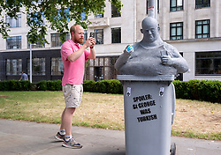 """© Licensed to London News Pictures; 15/06/2020; Bristol, UK. People view and photograph a new mystery statue of a caricature Englishman has been placed by the now empty Colston plinth on Monday morning, following an """"All Lives Matter"""" protest at the weekend to """"defend the Cenotaph"""". The grey statue shows a bald man resting in a wheelie bin with the words """"Spoiler: St George was Turkish"""" on the front. He is holding a small globe in one hand and a mobile phone in the other hand with a screen showing the St George flag and words """"England for the English"""". The character wears a string vest over a beer belly and looks over to where Colston's statue was torn down from its plinth a week ago. The artist is not known but the statue looks similar to """"Ruth"""", a character who appeared on Victoria Street in April 2018. This comes just over a week after the statue of Edward Colston which has stood in Bristol city centre for over 100 years was pulled down by protestors and thrown in Bristol Docks during a Black Lives Matters rally and march through the city centre. The rally was held in memory of George Floyd, a black man who was killed on May 25, 2020 in Minneapolis in the US by a white police officer kneeling on his neck for nearly 9 minutes. The killing of George Floyd has seen widespread protests in the US, the UK and other countries against both modern day racism and historical legacies of slavery. Edward Colston (1636 – 1721) was a wealthy Bristol-born English merchant involved in the slave trade, a Member of Parliament and a philanthropist. He supported and endowed schools, almshouses, hospitals and churches in Bristol, London and elsewhere, and his name is commemorated in several Bristol landmarks, streets, three schools and the Colston bun. Photo credit: Simon Chapman/LNP."""
