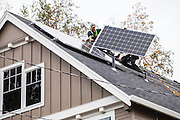 A crew from Synchro Solar installs panels on a home in Portland, OR. Photographed for Energy Trust of Oregon.