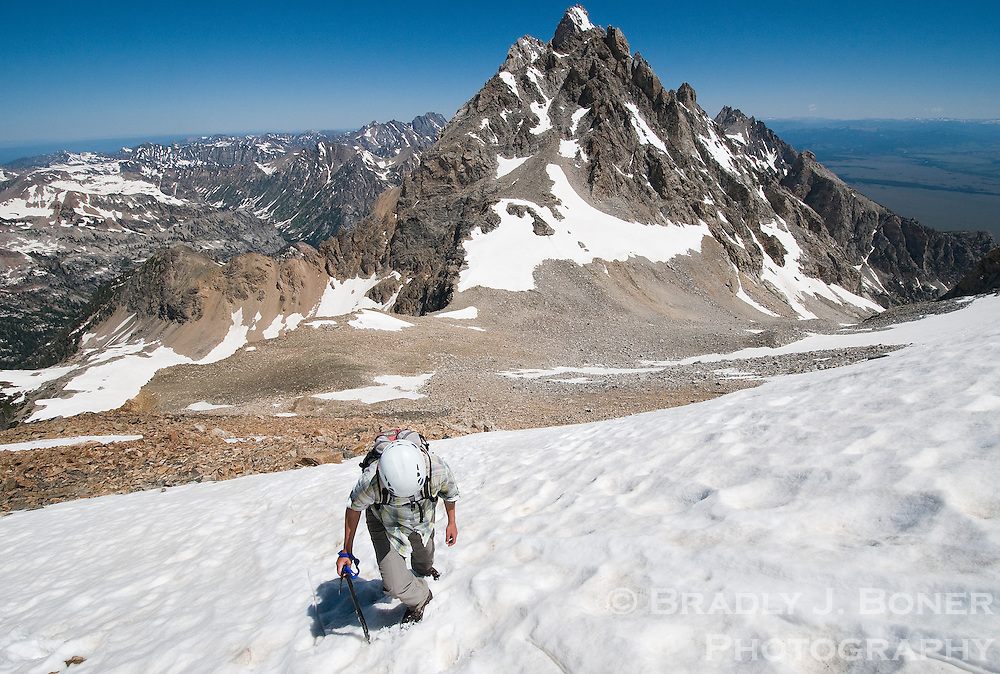 A climber ascends the upper snowfield of the South Teton during a successful ascent of the peak in Grand Teton National Park. The Middle Teton and upper portion of the Grand Teton are visible in the distance.