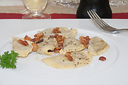 ravioli mezzelune, egg pasta with eggplant filling on white dish, red wine,glass and fork, modern italian food