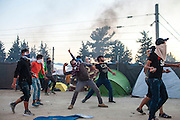 19 May 2016, Idomeni, Greece -Refugees pushed a train towards a police line during a protest at Camp Idomeni, after which clashes ensued. Protesters threw rocks and police retaliated with tear gas.