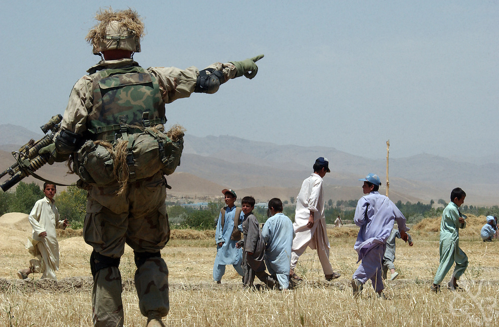 A U.S. Army soldier from the 101st Airborne clears an airfield of Afghan youths as an inbound Blackhawk helicopter approaches July 16, 2002 in village of Hesarak, eastern Afghanistan. The army raided the village to conduct a follow-up search for possible Al-Qaida or Taliban intelligence materials and to provide humanitarian aid. The raid was a follow-up to a similar raid there four days ago that yielded two detainees and undisclosed intelligence materials.