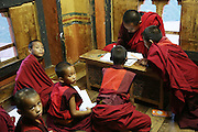 Young Buddhist monks in classroom with teacher at Nalanda Buddhist Monastery, Punakha, Bhutan..Bhutan the country that prides itself on the development of 'Gross National Happiness' rather than GNP. This attitude pervades education, government, proclamations by royalty and politicians alike, and in the daily life of Bhutanese people. Strong adherence and respect for a royal family and Buddhism, mean the people generally follow what they are told and taught. There are of course contradictions between the modern and tradional world more often seen in urban rather than rural contexts. Phallic images of huge penises adorn the traditional homes, surrounded by animal spirits; Gross National Penis. Slow development, and fending off the modern world, television only introduced ten years ago, the lack of intrusive tourism, as tourists need to pay a daily minimum entry of $250, ecotourism for the rich, leaves a relatively unworldly populace, but with very high literacy, good health service and payments to peasants to not kill wild animals, or misuse forest, enables sustainable development and protects the country's natural heritage. Whilst various hydro-electric schemes, cash crops including apples, pull in import revenue, and Bhutan is helped with aid from the international community. Its population is only a meagre 700,000. Indian and Nepalese workers carry out the menial road and construction work.