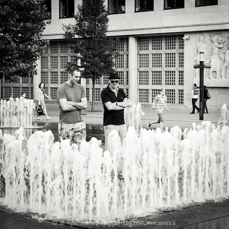 Two men admiring the sensor controled fountain in central Budapest Hungary