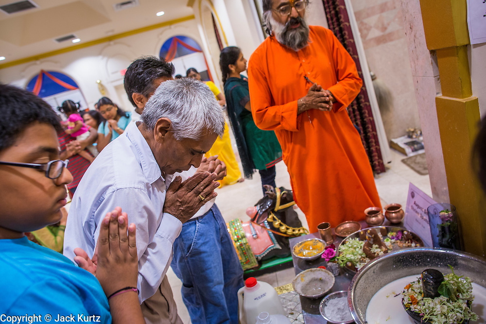10 AUGUST 2012 - PHOENIX, AZ:   People pray at the mandirs that house shrines in the temple during the celebration of Janmashtami at Ekta Mandir, a Hindu temple in central Phoenix. Janmashtami is the Hindu holy day that celebrates the birth of Lord Krishna. Hindu communities around the world celebrate the holy day. In Arizona, most of the Hindu temples in the Phoenix area have special celebrations of the day.    PHOTO BY JACK KURTZ