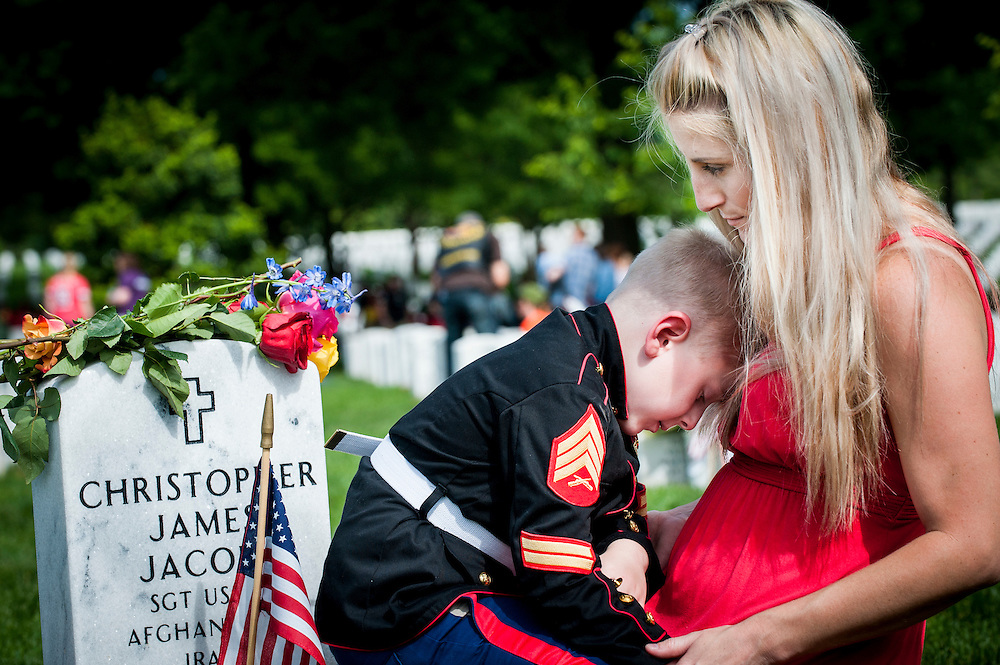 On Memorial Day, Christian Jacobs, 5, of Hertford, NC, rests his head on his mother, Brittany, at the headstone of his father, Marine Sgt. Christopher Jacobs, in Section 60 at Arlington National Cemetery in Arlington, Virginia, USA, on 30 May 2016.