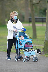 ©Licensed to London News Pictures 31/03/2020  <br /> Greenwich, UK. A lady walking her dog with a mask on. People get out of the house from Coronavirus lockdown to exercise in Greenwich Park, London. The Prime Minister Boris Johnson has asked people to stay at home to help in the fight against Covid-19 and to only go out for essential reasons. credit:Grant Falvey/LNP