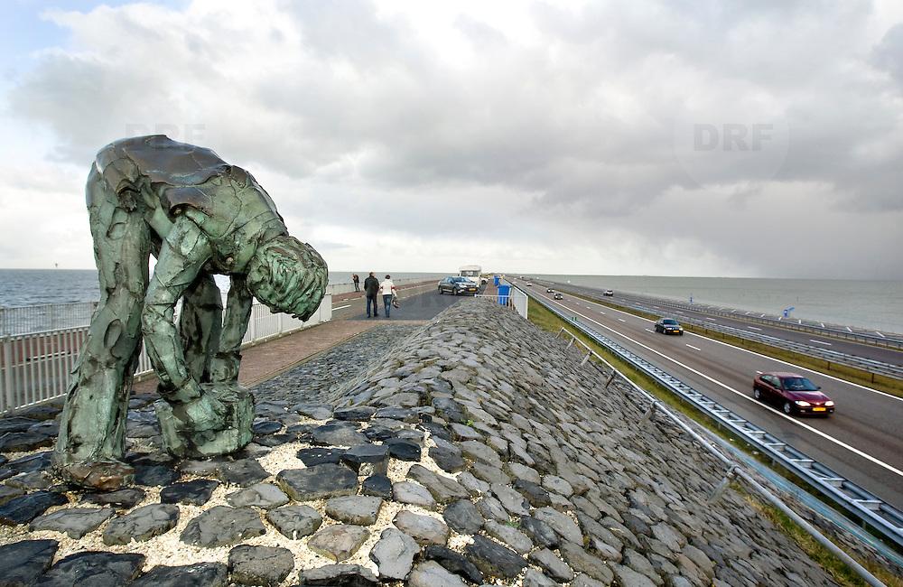 """Nederland Den Oever Zurich 22 november 2008 20081122 Foto: David Rozing ..Serie afsluitdijk. De Afsluitdijk is een belangrijke waterkering en verkeersweg in Nederland. De waterkering sluit het IJsselmeer af van de Waddenzee. Hieraan ontleent de dijk zijn naam. De verkeersweg, onderdeel van Rijksweg a7, verbindt Noord-Holland met Friesland...afsluitdijk ter hoogte van de uitkijktoren. Bronzen beeld Steenzetter.Ter gelegenheid van 50 jaar Afsluitdijk werd in 1982 het beeld de """"Steenzetter"""" van Ineke van Dijk geplaatst. Tekst: """" de strijd tegen het water blijft een strijd door en voor de mens """" weg, snelweg, wegen, auto, auto's, dijkweg  deltaplan...Foto David Rozing"""