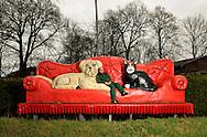 """Jens van Yperen on his over-sized couch along with a dog and a cat. This couch is the logo and symbol of the kennel in Brokenlande. The owner Jens van Yperen took over the dog hotel from his father in 1998. The family business exists since 1976. He is trained zookeeper and dog trainer and grew up with animals. One of his statements: """"A dog is not a child replacement, rather it is a prince, a little king."""" Brokenlande, Germany / Jens van Yperen auf seiner ueberdimensionierten Couch zusammen mit Hund und Katze. Diese Couch ist Logo und Symbol des Hundehotels in Brokenlande. Der Besitzer Jens van Yperen hat 1998 das Hundehotel von seinem Vater uebernommen. Dieser Familienbetrieb besteht sein 1976. Er ist gelernter Tierpfleger und Hundetrainer und mit Tieren aufgewachsen. Eines seiner Statements: """"Ein Hund ist kein Kindersatz, er ist vielmehr ein Prinz, ein kleiner Koenig"""". Brokenlande, Deutschland"""