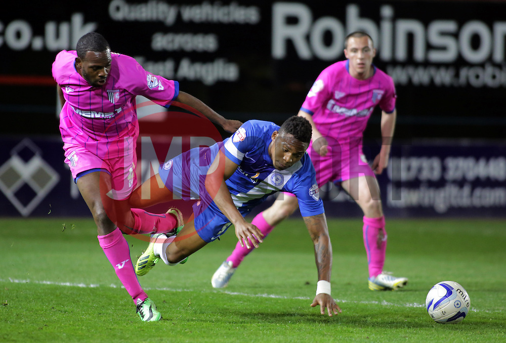 Peterborough United's Britt Assombalonga is fouled by Gillingham's Myles Weston  - Photo mandatory by-line: Joe Dent/JMP - Mobile: 07966 386802 08/04/2014 - SPORT - FOOTBALL - Peterborough - London Road Stadium - Peterborough United v Gillingham - Sky Bet League One