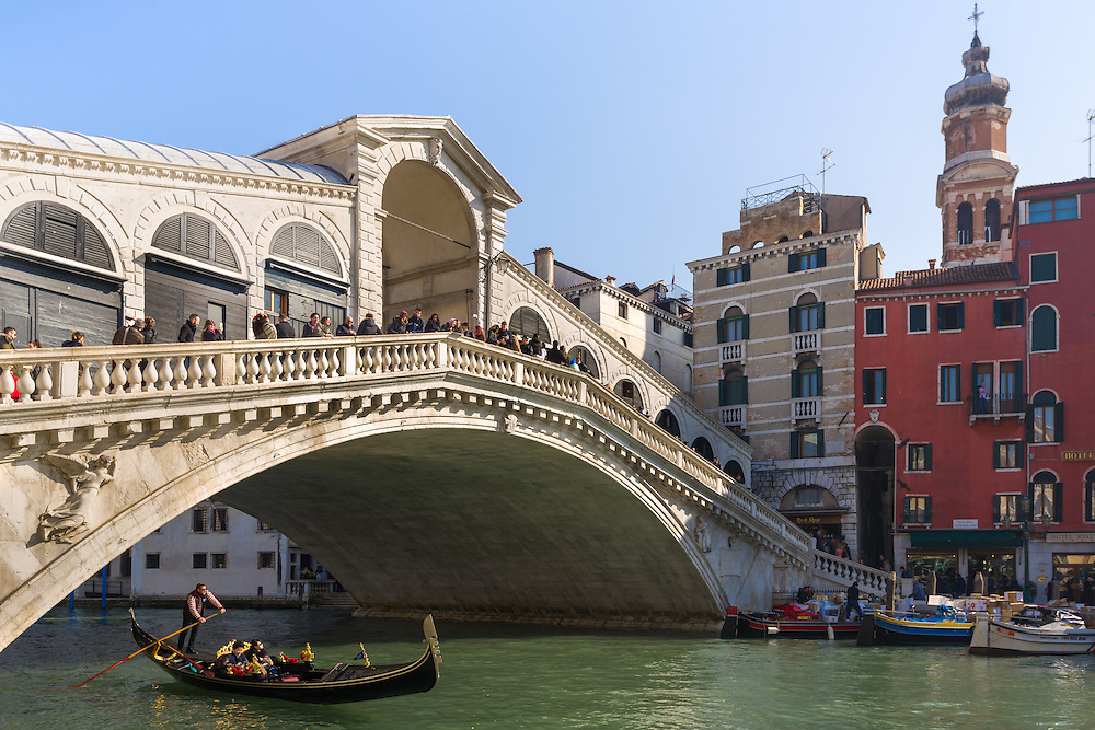 a gondolier is seen taking two passengers in a gondola under the rialto bridge in venice