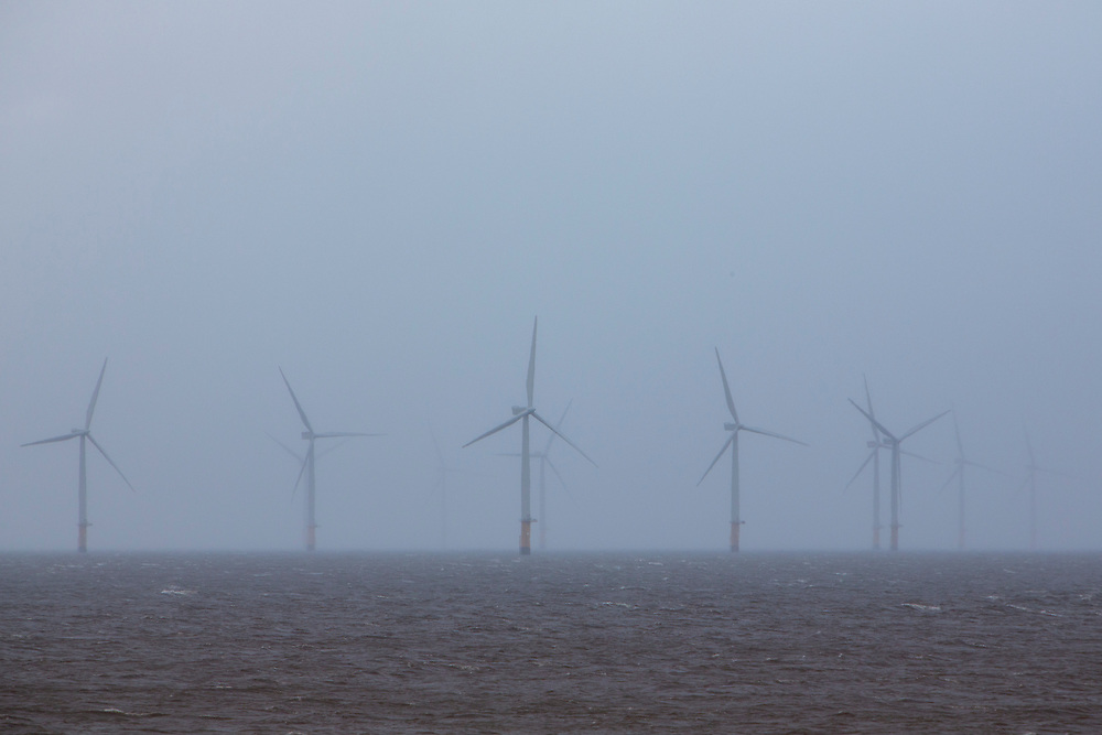 The Lincs Wind Farm breaking through the rain clouds. It is a 270 MW offshore wind farm 8 kilometres (5.0 mi) off Skegness Lincolnshire, on the east coast of England in the North Sea. It cost over £1 billion to build including electrical transmission links and was completed in 2013. Skegness, Lincolnshire, United Kingdom.  (photo by Andrew Aitchison / In pictures via Getty Images)