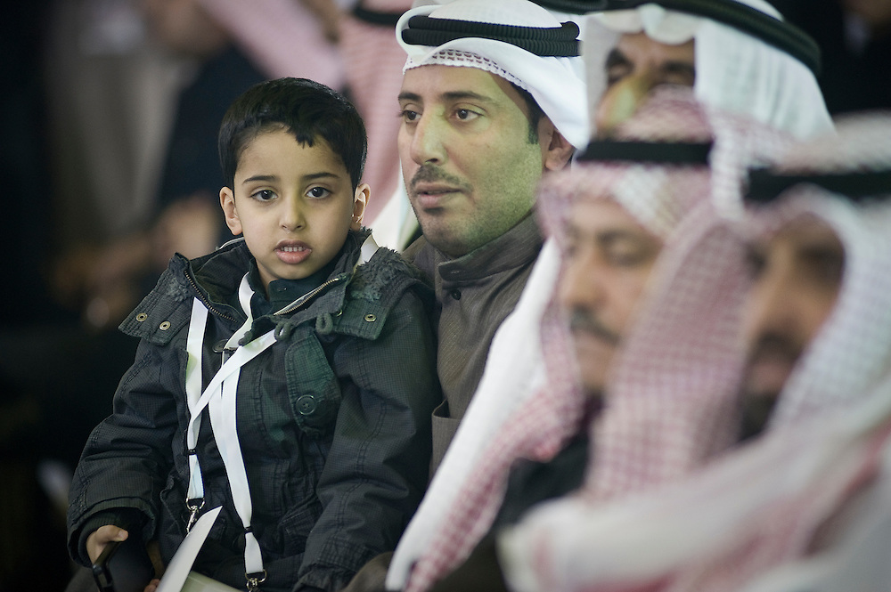 A Kuwaiti man with his young son in a crowd during a Jan. 23 election rally near Kuwait City organized by candidate Anwar Al-Dahoum.  More than 400,000 Kuwaiti men and women are eligible to cast ballots to choose from among some 320 men and women candidates currently in the running in the February 2, 2012 parliamentary polls to elect a new 50-member National Assembly (parliament).