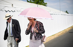 © Licensed to London News Pictures. 04/07/2018. Henley-on-Thames, UK. A woman shelters form the sun underneath her umbrella on day one of the Henley Royal Regatta, set on the River Thames by the town of Henley-on-Thames in England. Established in 1839, the five day international rowing event, raced over a course of 2,112 meters (1 mile 550 yards), is considered an important part of the English social season. Photo credit: Ben Cawthra/LNP