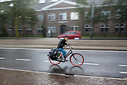 Een jongen fietst in de regen door de Sarphatistraat in Amsterdam.<br /> <br /> A boy is cycling in the rain at the Sarphatistraat in Amsterdam
