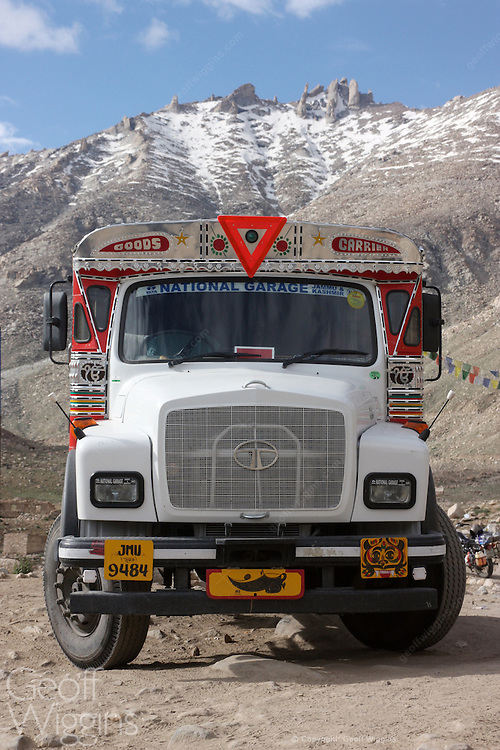 Decorated Tata truck parked below the snow capped mountains on the highest road in the world in the Himalayas Pang, Ladakh, northern India