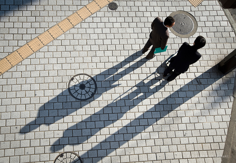 Overhead view of businessmen and shadows on sidewalk near the Ginza street crossing, Kumamoto city, Kumamoto Prefecture, Japan